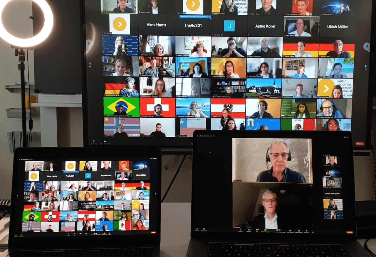 drei Bildschimre und eine Lampe sind zu sehen. Auf den Bildschirmen ist ein Sprecher sichtbar - auf den anderen Bildschirmen viele Menschen in einer Vidokonferenz, viele haben als Hintergrund in der Videokonferenz eine Flagge eingefügt. Es sind pro Bildschirm ca. 50 Köpfe zu sehen